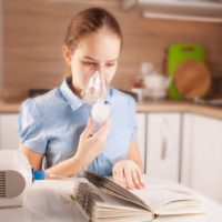 Girl with asthma using inhaler and reading book in the kitchen